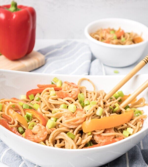 Styled shot of finished easy shrimp lo mein recipe ready to be served with a bowl and a red pepper in the background