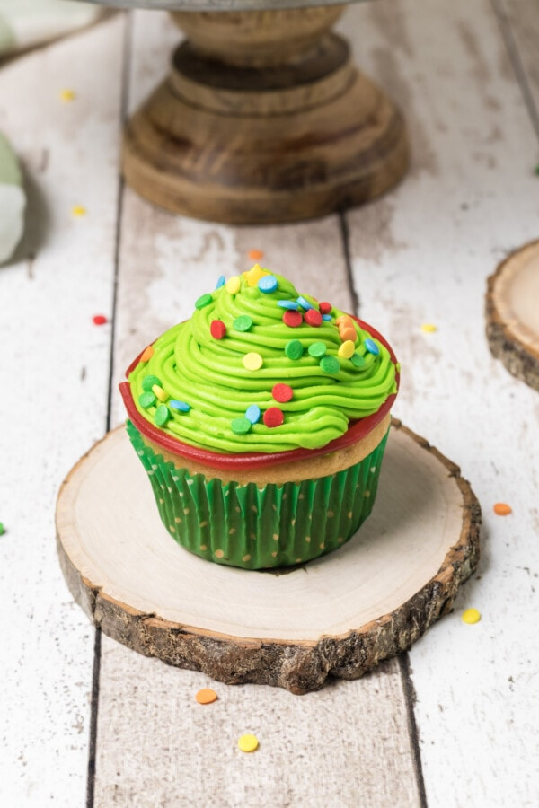 Styled photograph of completed Christmas Tree cupcakes. One is perfectly in focus while others are just out of the shot.