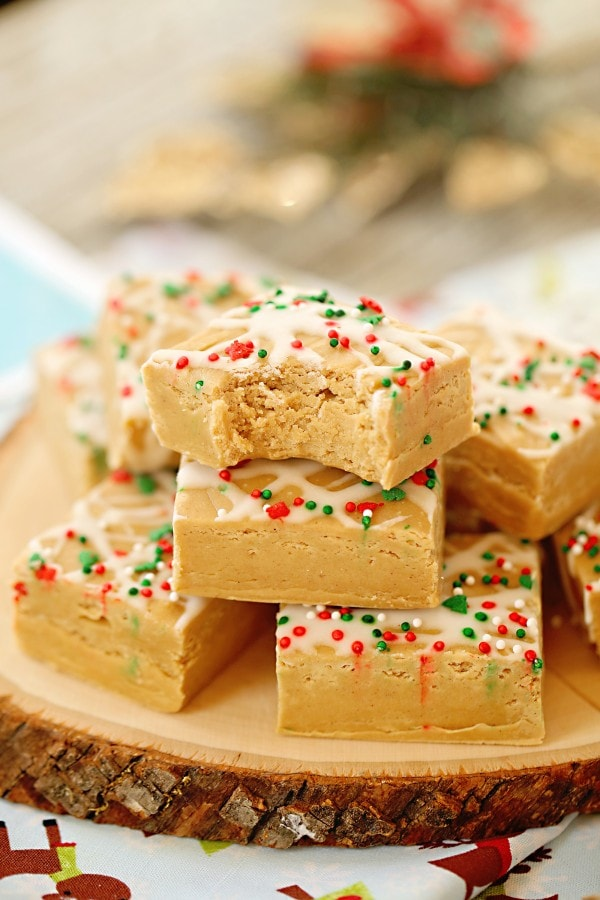 Gingerbread fudge piled on a slice of a tree with a bite out of the front square.