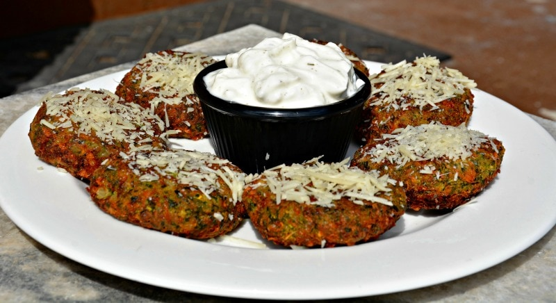 An old picture that shows what Cheesy Zucchini Cakes look like that use grated zucchini and not shredded. Zucchini Fritters are covered in parmesan cheese on a white plate with sour cream dip in the middle of the plate in a black cup.
