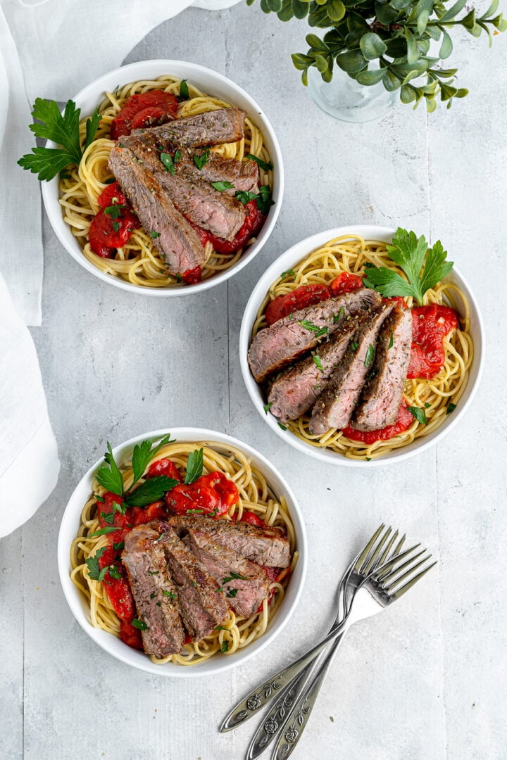 three bowls filled with spaghetti topped with homemade marinara sauce and sliced steak