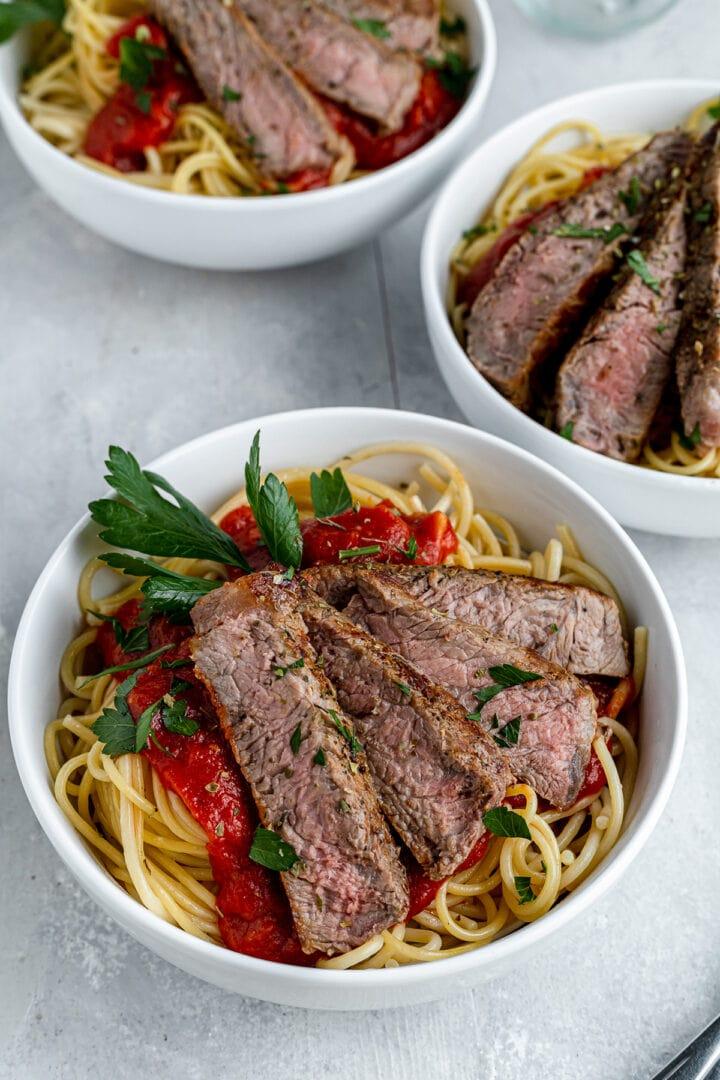 three bowls of pasta with homemade marinara sauce and steak