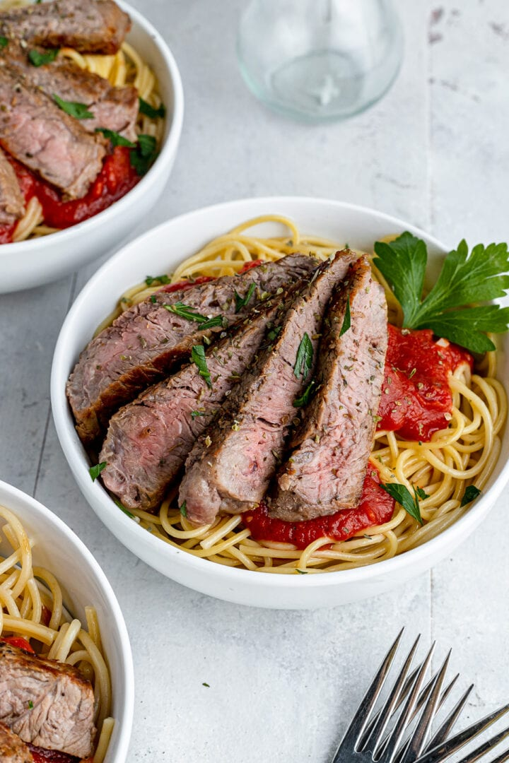 a picture of pasta with steak and homemade marinara sauce