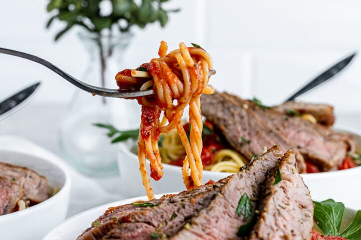 a bite of spaghetti on a fork above a bowl of sliced steak and pasta.