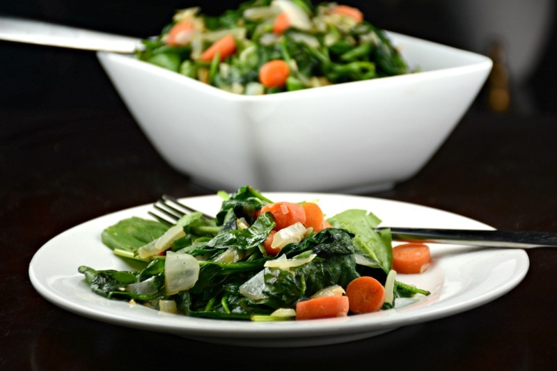 Sauteed spinach and carrots with fork on white plate with white bowl of spinach and carrots in background.