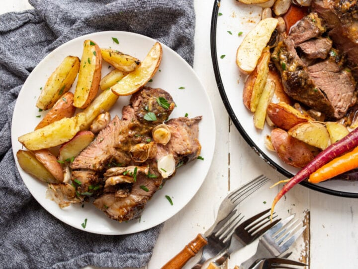 Overhead shot of air fryer roast beef and potatoes on plate next to serving dish with more air fried roast beef.