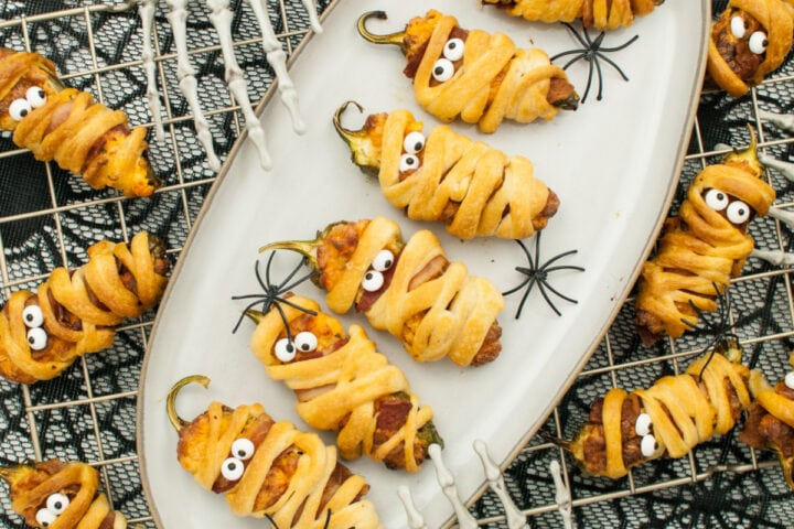 Overhead shot of air fryer Halloween jalapeno poppers on white serving plate with more poppers surrounding it