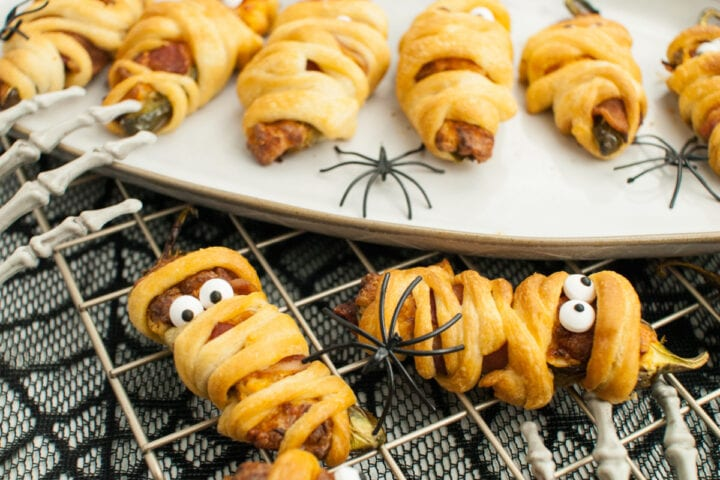 Closeup shot of two air fryer jalapeno poppers with more Halloween mummy jalapeno poppers on serving tray