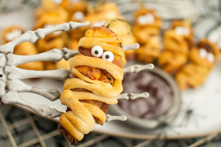 Skeleton hand holding air fryer jalapeno popper with more Halloween mummy jalapeno poppers below