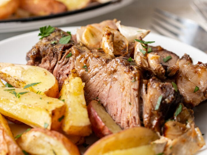 Closeup shot of air fried roast beef and potatoes on white plate
