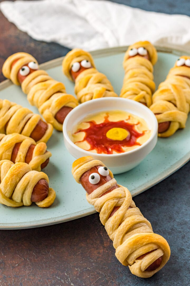 Closeup shot of mummy pigs in a blanket with dipping sauce on plate.