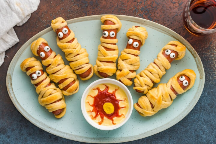 Overhead shot of mummy hot dogs with bloodshot eye sauce on plate.