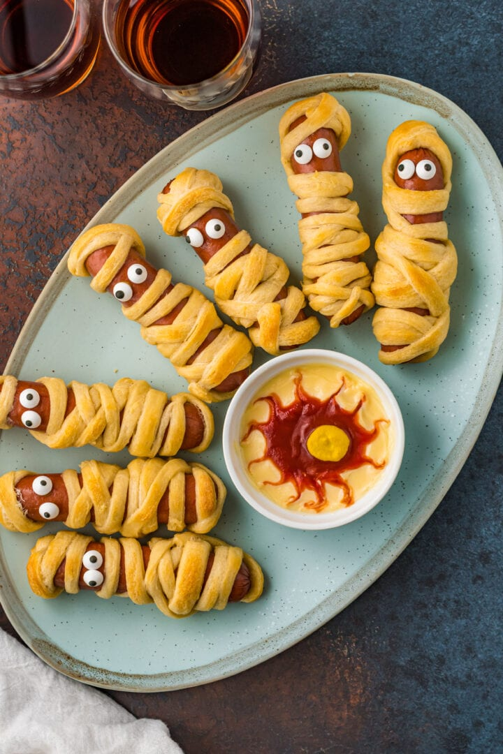 Overhead shot of Halloween hot dogs with dipping sauce on plate