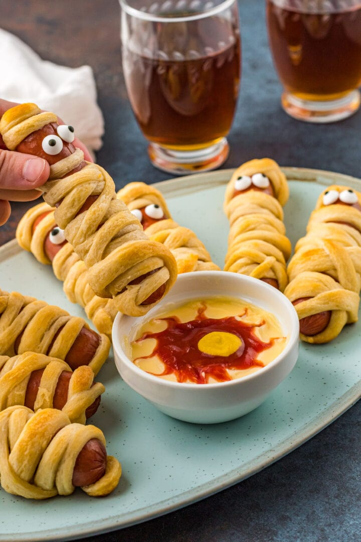 Halloween hot dog being held over plate with more mummy hot dogs and dipping sauce on plate