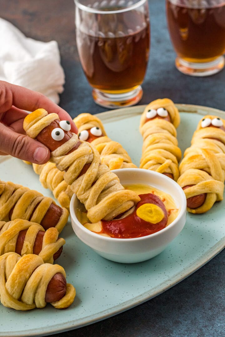 Mummy pigs in a blanket on plate with one mummy hot dog being dipped in bowl of dipping sauce