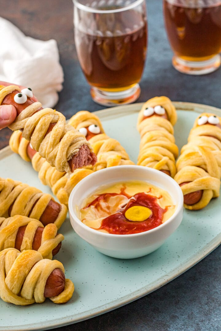 Mummy hot dogs on plate with dipping sauce and another mummy dog being held over them with bite taken out