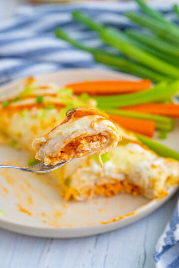 buffalo chicken enchilada on a white plate with a bite on a fork whole green onions in the background.