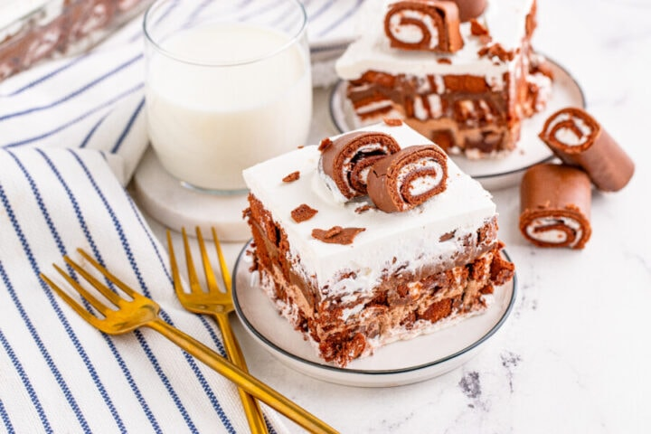 Two plates with a slice of Swiss Roll lush cake on each next to glass of milk