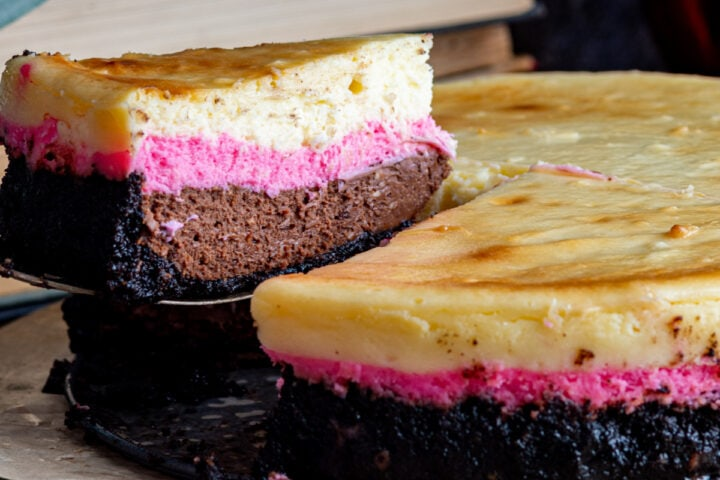 Closeup shot of slice of neapolitan cheesecake being removed from triple layer cheesecake