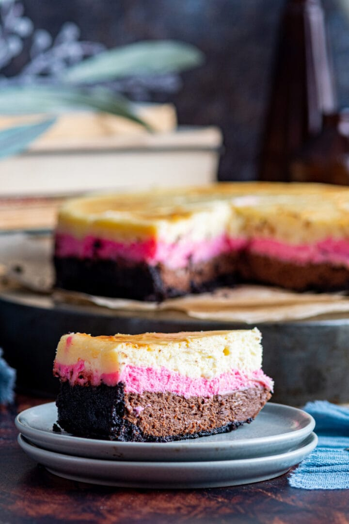 Slice of neapolitan cheesecake on plate with more cheesecake in background