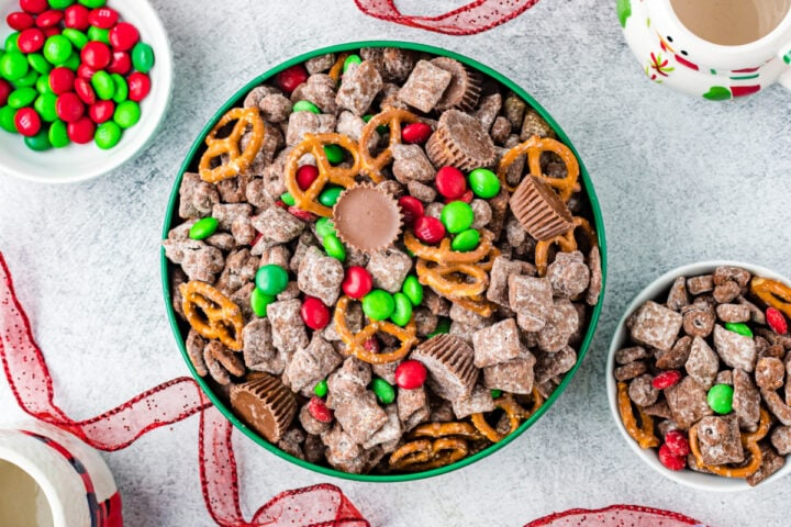 Overhead shot of reindeer chow in tin next to a bowl of more Christmas puppy chow