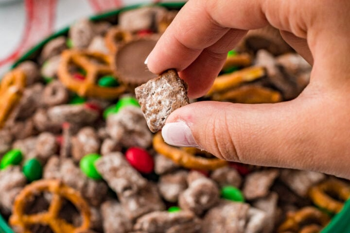 Hand holding a piece of reindeer chow over bowl of more Christmas puppy chow