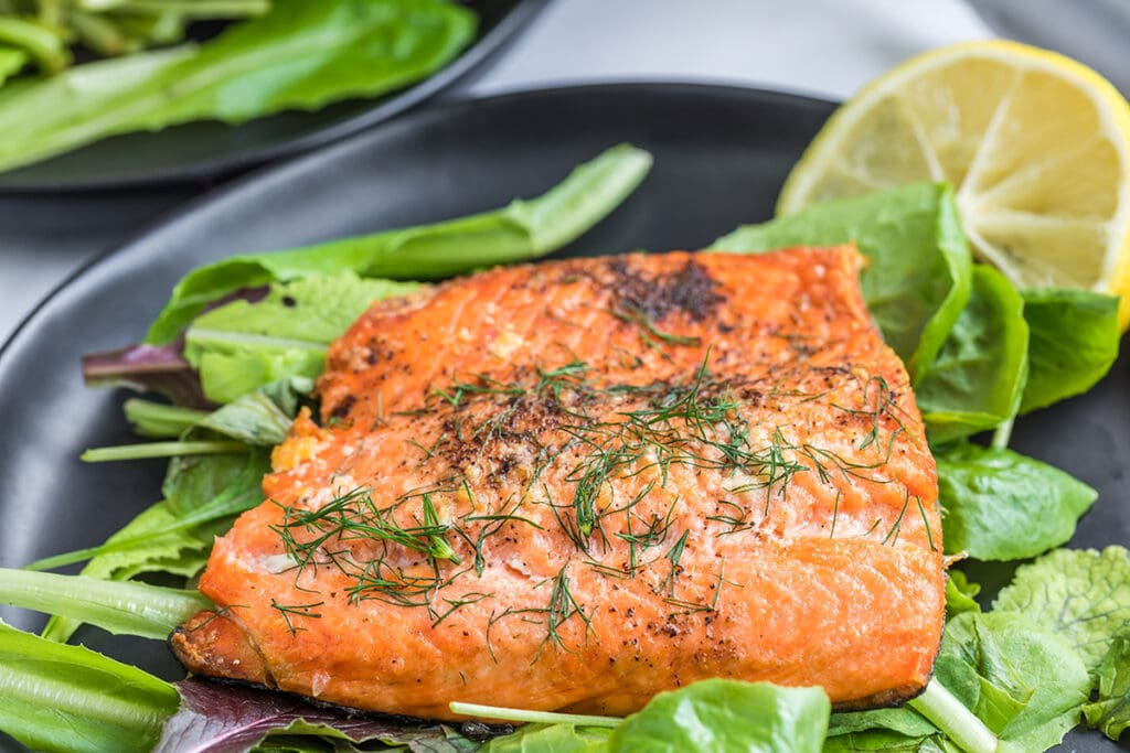 close up side view image of smoked salmon fillet on a dark gray plate.