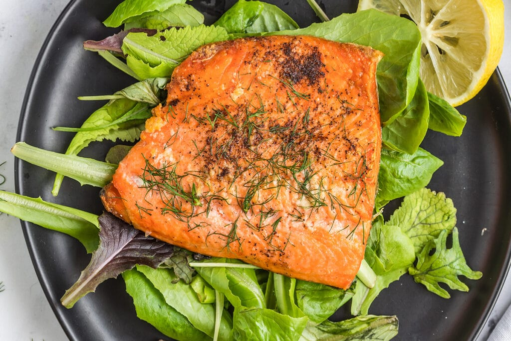 salmon fillet on a black plate that is covered in spring mix and a slice of lemon.