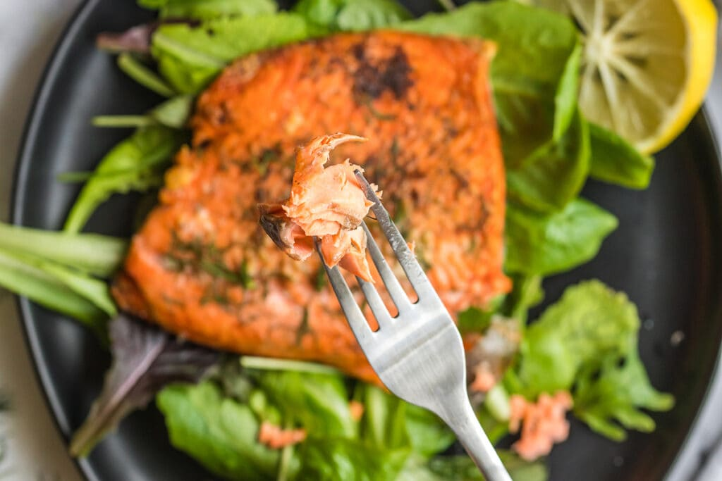 sliver fork with a piece of air fryer frozen salmon bite on it.