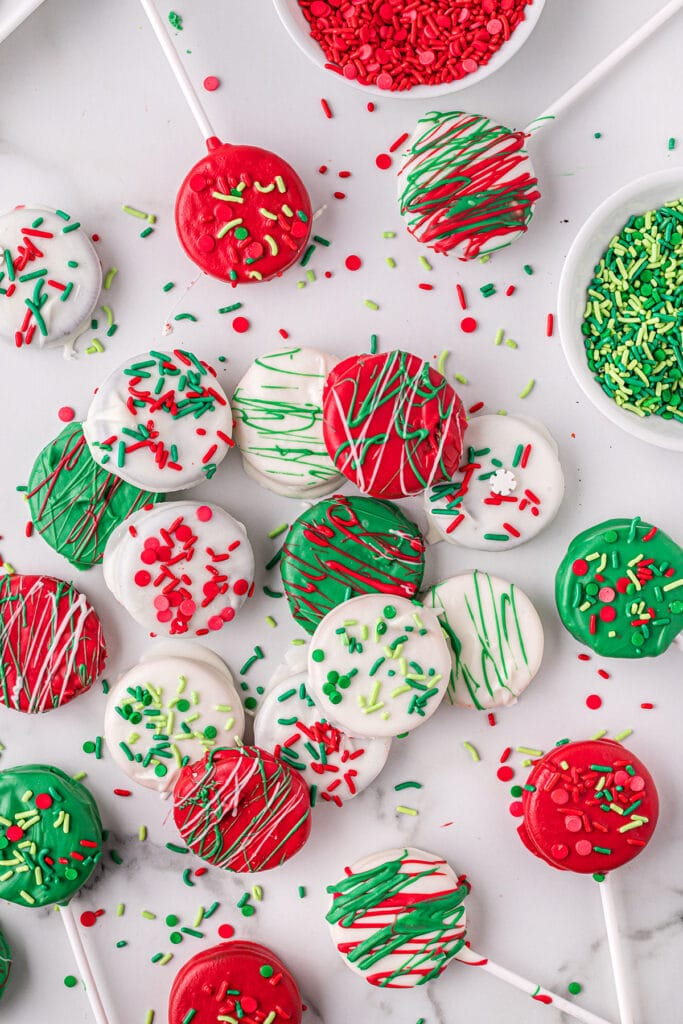 Oreos dipped in red, green and white chocolate spread out on a white table.