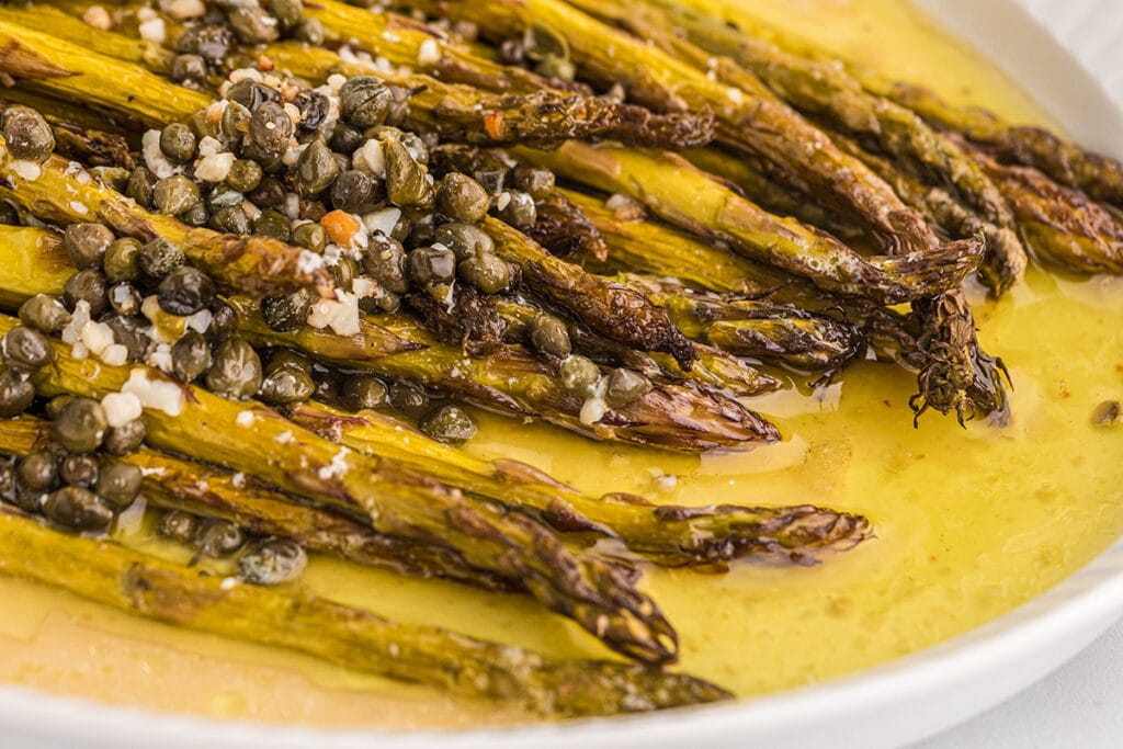 close up of a Plate of smoked asparagus topped with capers.