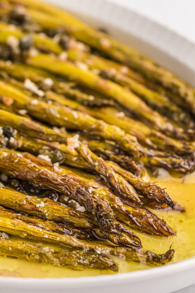close up of a plate of smoked asparagus in olive oil,