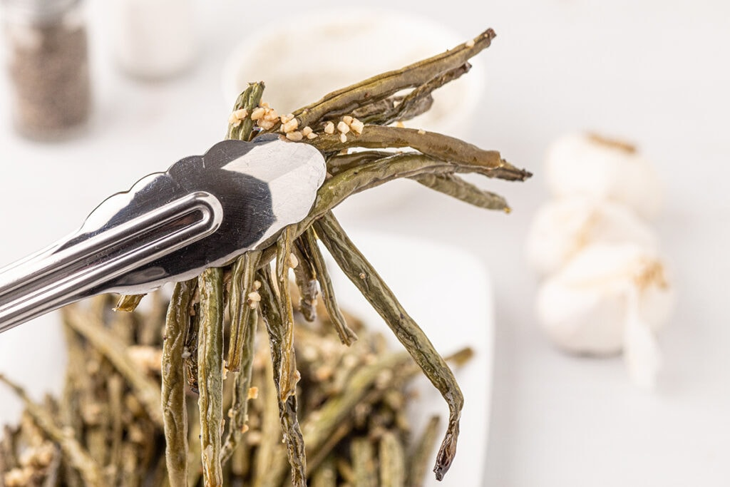 smoked green beans coated in butter and garlic held in the air with a pair of sliver metal tongs,