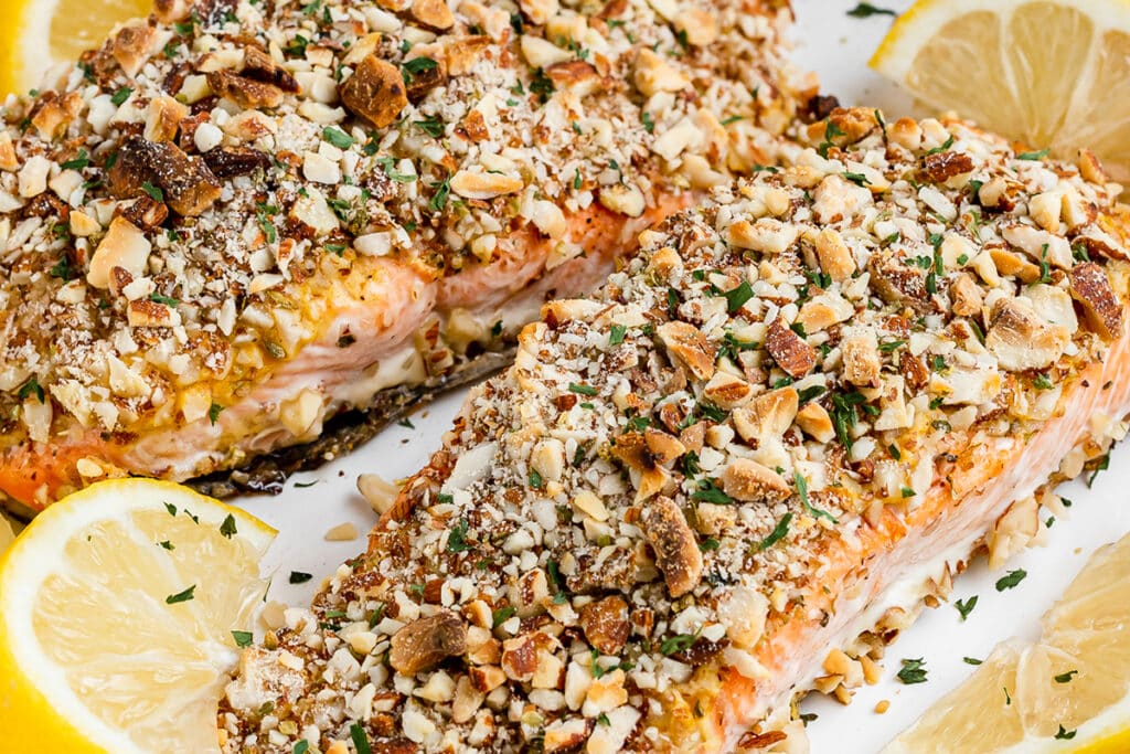 zoomed in image of a plank of salmon that has been topped with crushed almonds and a savory dijon sauce.