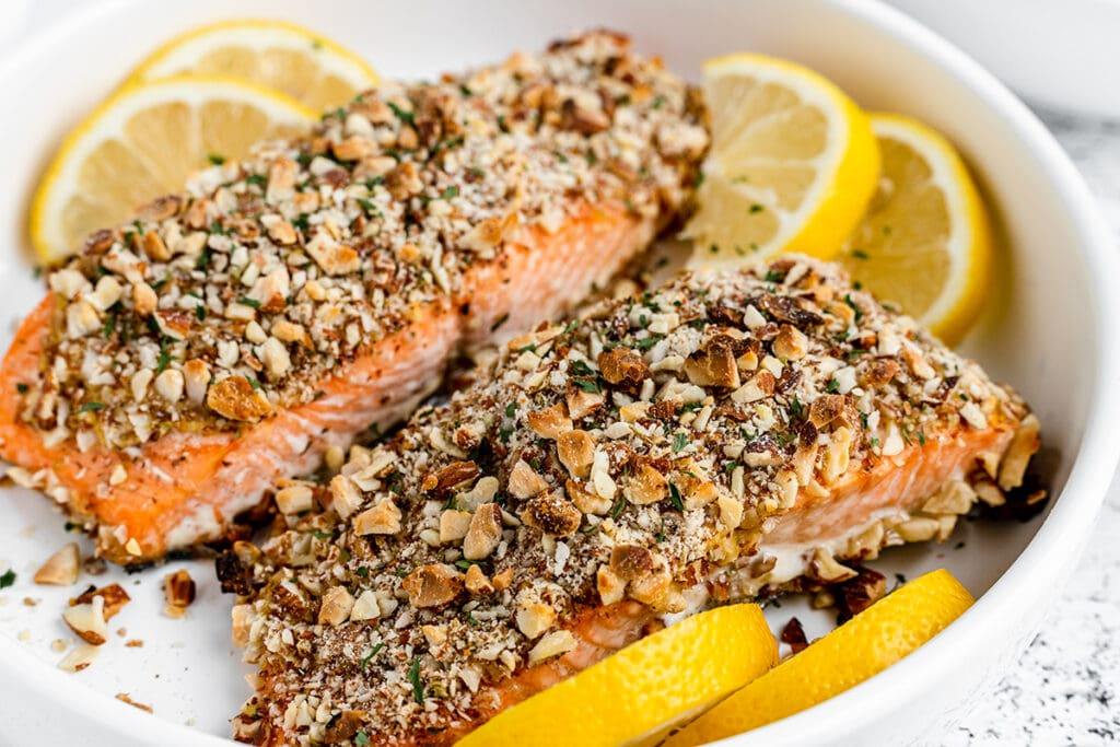 two pieces of fish crusted in crushed almonds, and a dijon sauce on a white plate with lemon slices.