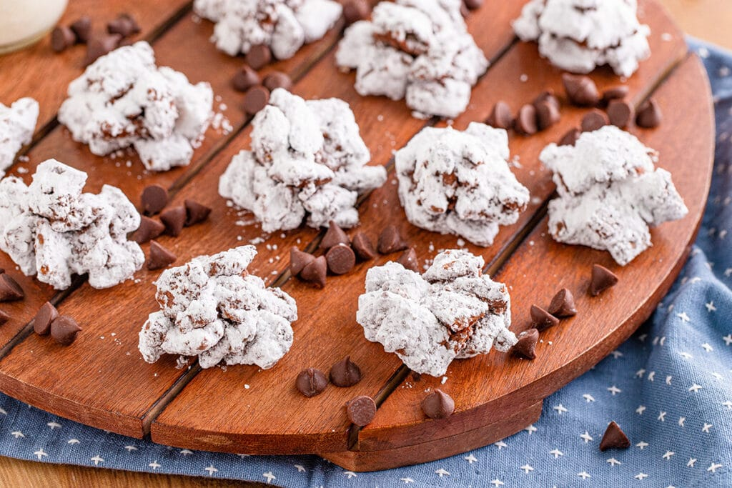 eleven peanut butter muddy buddy cookies on a wooden cutting board with chocolate chips sprinkled around.