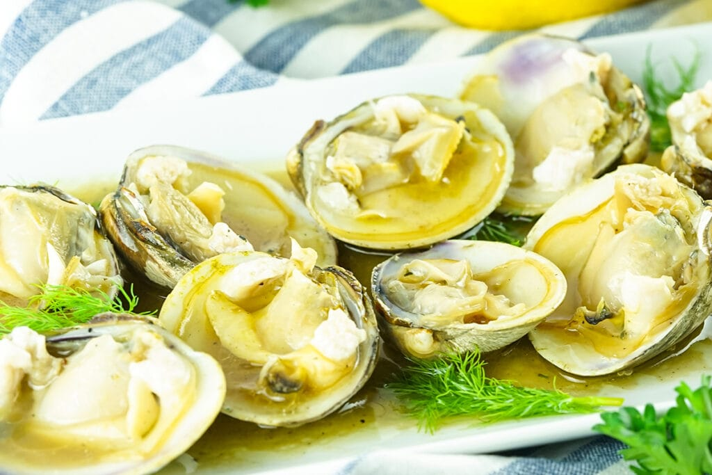 plate of fresh smoked clams coated in a white wine and butter dill sauce on a white rectangle plate.