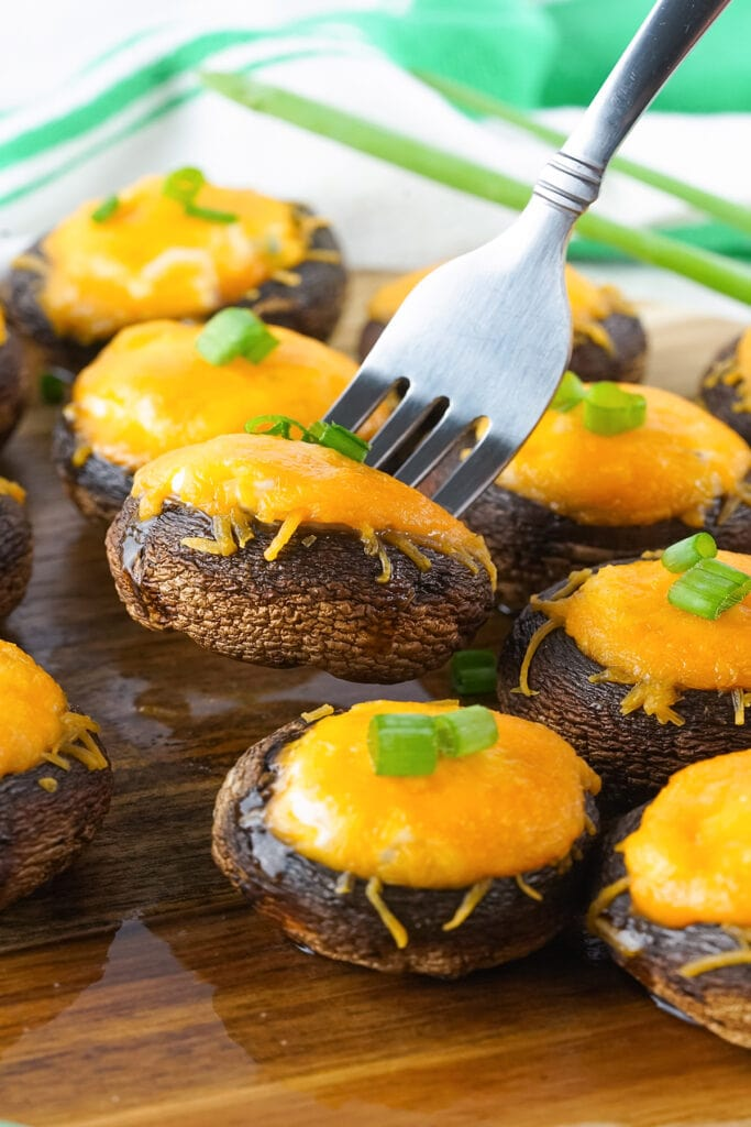 Mini smoked stuffed mushrooms on a wooden cutting board, with one mushroom on a sliver fork.
