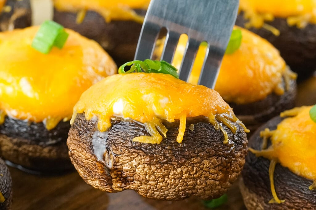 smoked stuffed mushroom topped with melted cheese with a sliver fork.