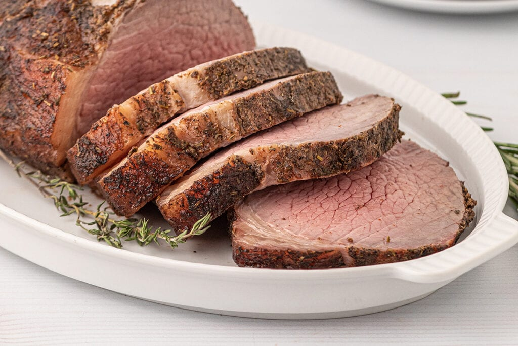sliced eye smoked and seasoned eye of round roast on a white platter with herbs around it
