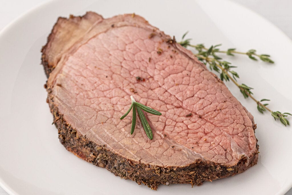 single slice of eye of round roast in a white plate with fresh herbs on the plate and on top.