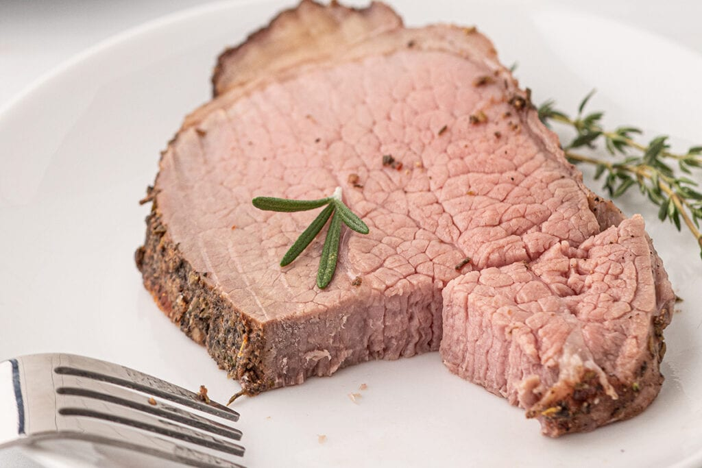 slice of smoked eye of round roast on a white plate with a bite missing.