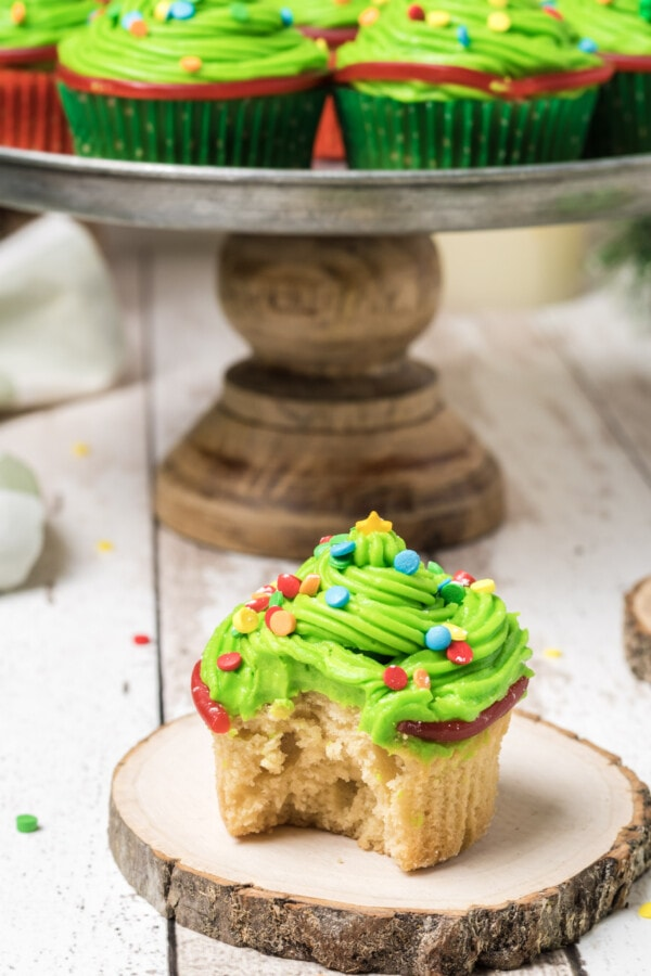 Finished Christmas tree cupcakes with one taken off the serving platter and sitting on a wooden coaster with a bite taken out of it.