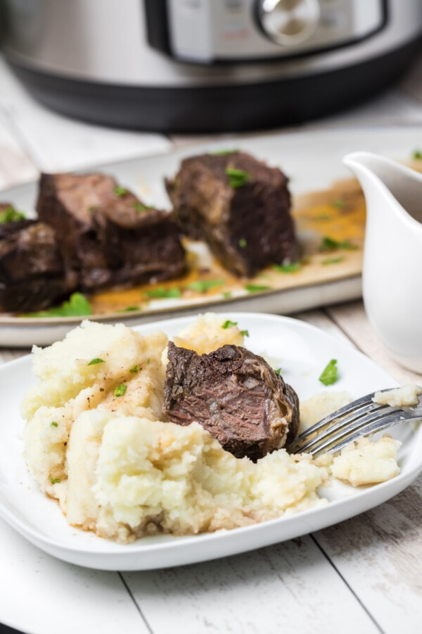 Beef rib over mashed potatoes on white plate with more ribs on white serving plate in background