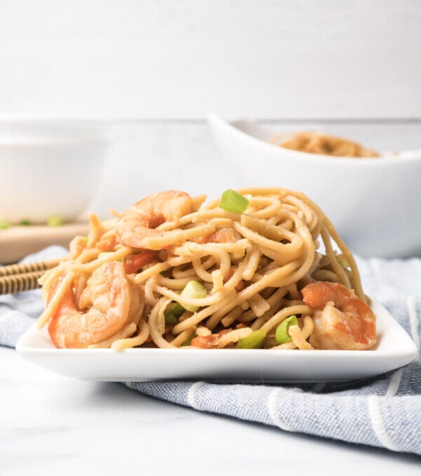 beautifully styled square plate on a cloth napkin piled high with chinese shrimp lo mein with green onions as garnish