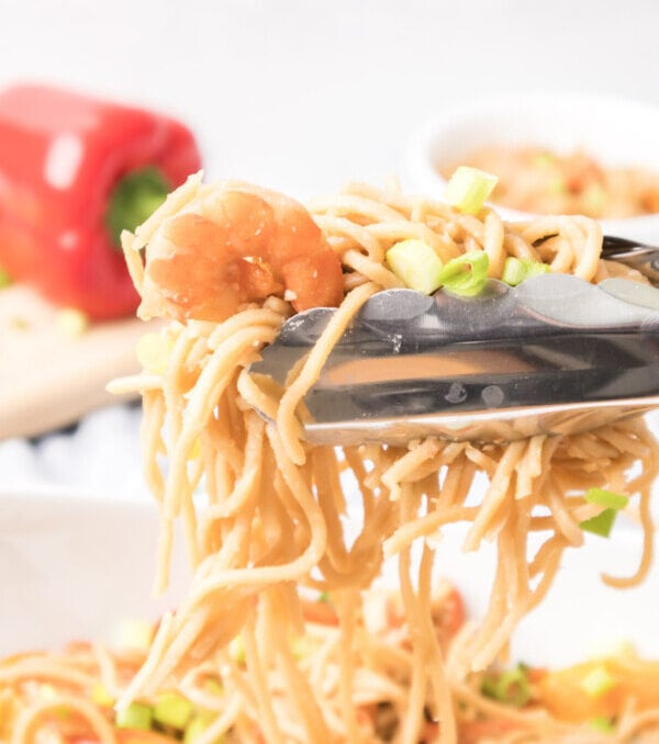 Tongs grabbing a serving of noodles, shrimp and green onions