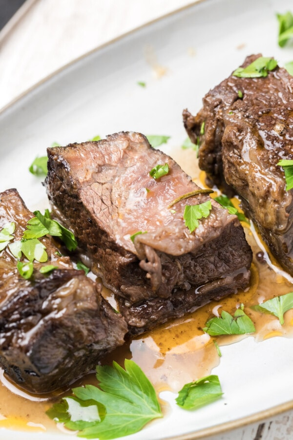 Closeup shot of short ribs on white plate