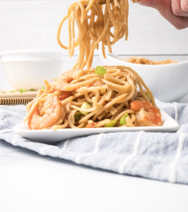 An action shot of Chinese shrimp lo mein being served