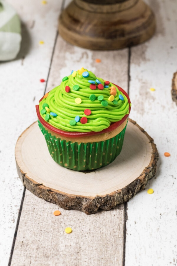 A single cupcake with green icing and colorful sprinkles decorated to look like a Christmas tree.
