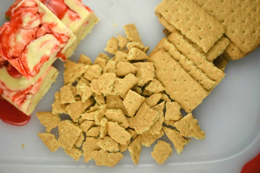3 Pieces of Strawberry Cheesecake Fudge with whole graham crackers and graham cracker pieces on a cutting board